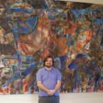 Jason Stallings standing in front of a large scale art commission after it's built and hung on site in the client's front entry way